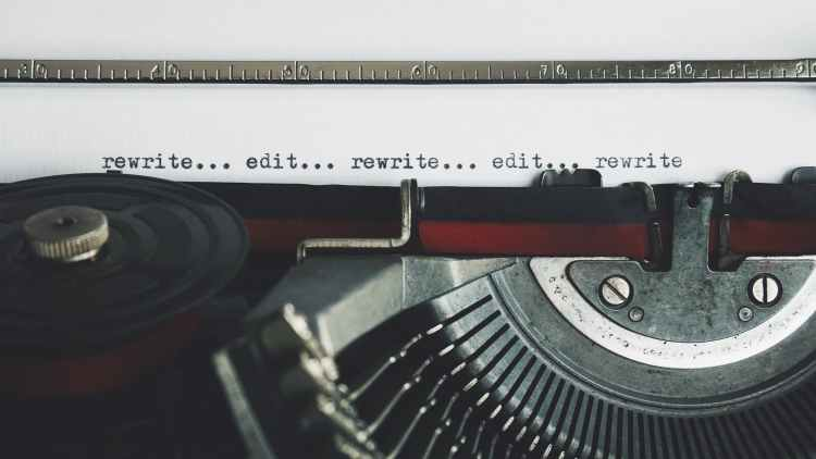 An old fashioned type-writer with the words rewrite and edit being typed.